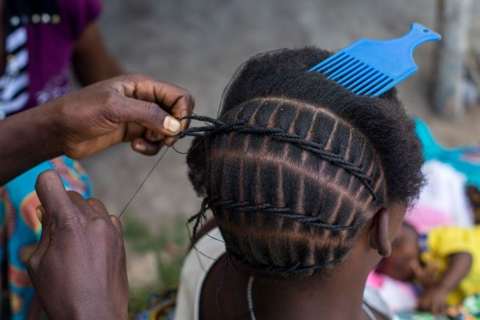 Mozambique: A woman gets her hair braided in northern Mozambique. More Info