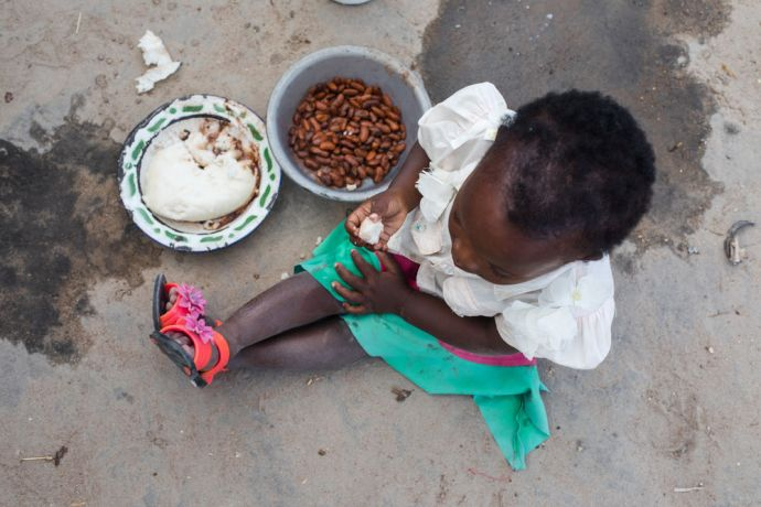 Mozambique: A little girl eats a meal of nshima and beans in northern Mozambique. More Info