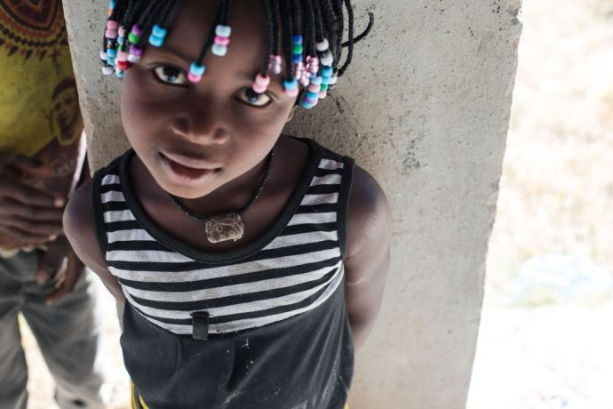 Mozambique: A young girl wears a charm around her neck for protection. Many children in northern Mozambique wear such necklaces from the time they are born. More Info