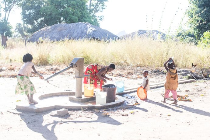 Mozambique: A young girl pumps water at a well in northern Mozambique. More Info