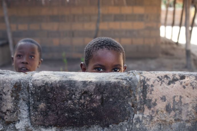 Mozambique: A child peers over a wall. More Info