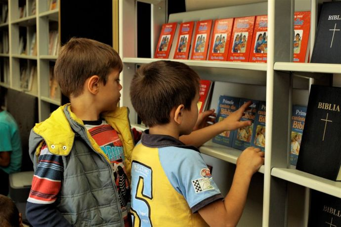 Moldova: Two boys browse through books at display inside Bus4Life. More Info