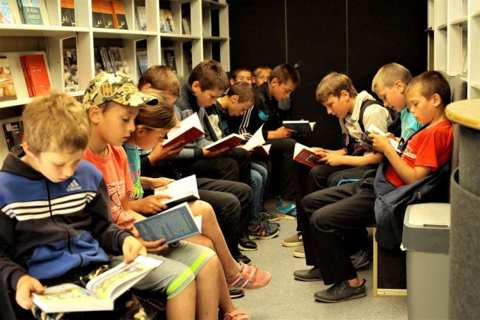 Moldova: Local children take time to read inside Bus4Life during an outreach in Northern Moldova. More Info
