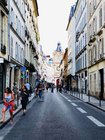 France: A narrow street in the center of Paris, lined with cafes, boutiques, and flower shops More Info