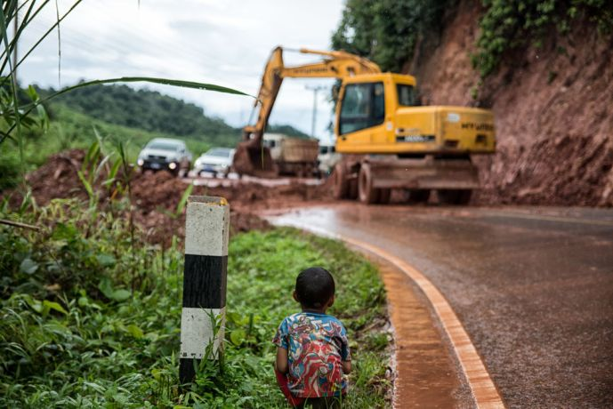 South East Asia: A small boy watches as a new mudslide is cleared from the road. More Info