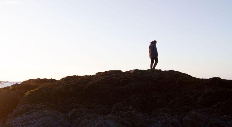 International: Person walks on top of rocks. More Info