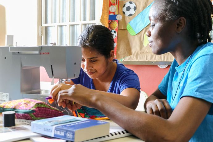 Panama: Balboa, Panama :: Latoya Letlow (Trinidad and Tobago) helps a woman learn to use a sewing machine. More Info