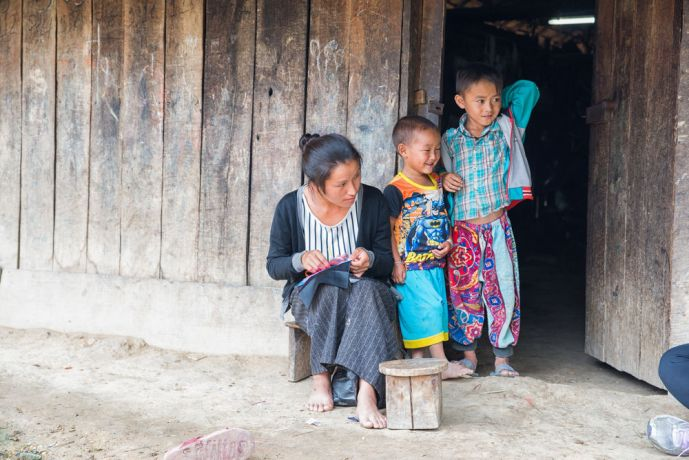 Laos: A mother sewing in the doorway with her children. More Info