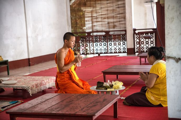 Laos: A monk blesses a woman after she brings a food offering to the temple. More Info