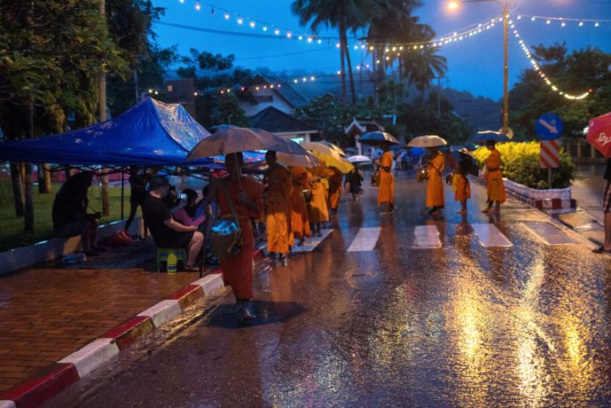 Laos: Monks begin their procession at 5:30 am and walk the streets around their temple collecting offerings, rain or shine. More Info