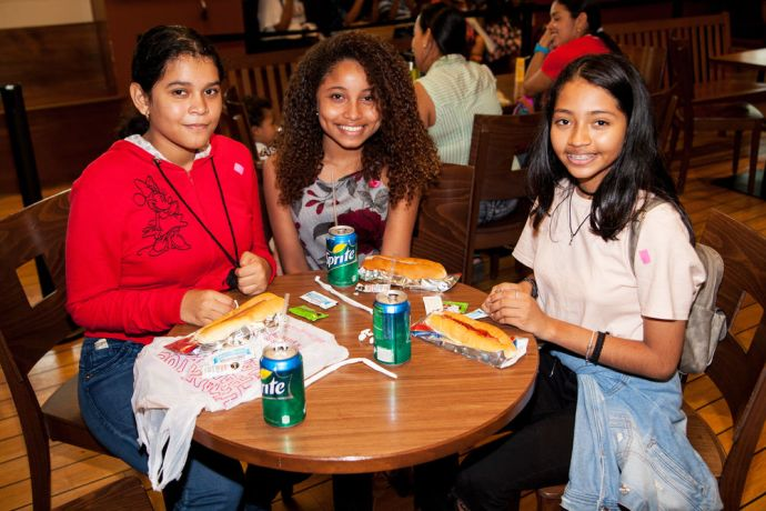 Panama: Balboa, Panama :: Three teenagers enjoy hotdogs at the international cafe on board Logos Hope. More Info