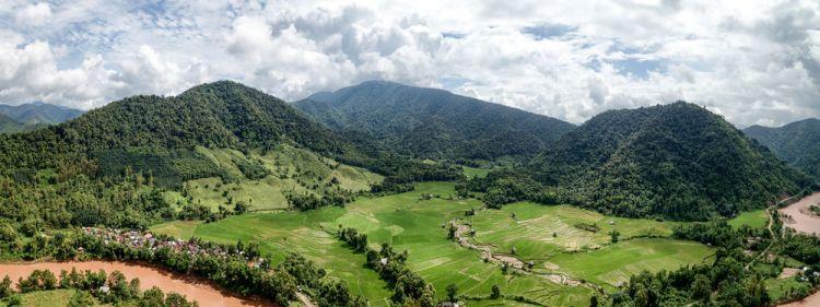Laos: The Mekong River running alongside rice fields. More Info