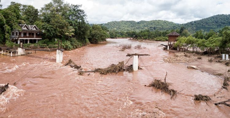 Laos: A muddy Mekong River flows past a broken bridge. More Info