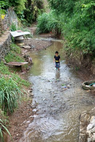Laos: A child plays in a stream. More Info