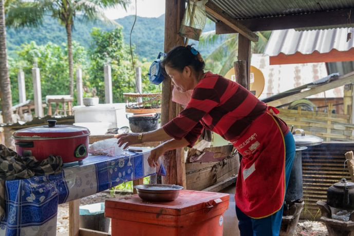 Laos: A woman prepares food for customers at her restaurant. More Info