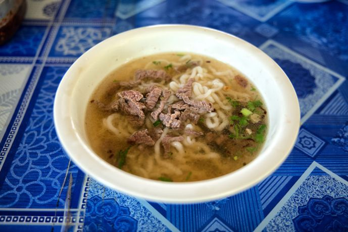 Laos: Noodle soup, the most common dish in Laos. This one has beef and blood curd. More Info