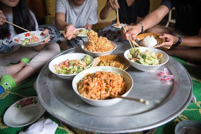 South East Asia: People enjoying a meal together in South East Asia. It is traditional for the food to placed in the middle and people take what they want with their chopsticks. More Info