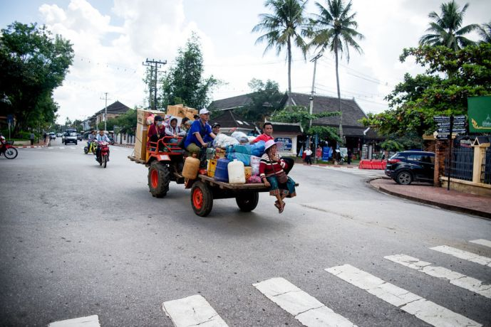 Laos: A group of people traveling in style on a tractor. More Info