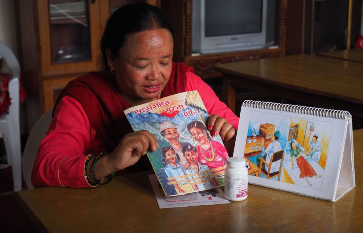 Nepal: An OM worker uses a book to teach about HIV and AIDS awareness. More Info