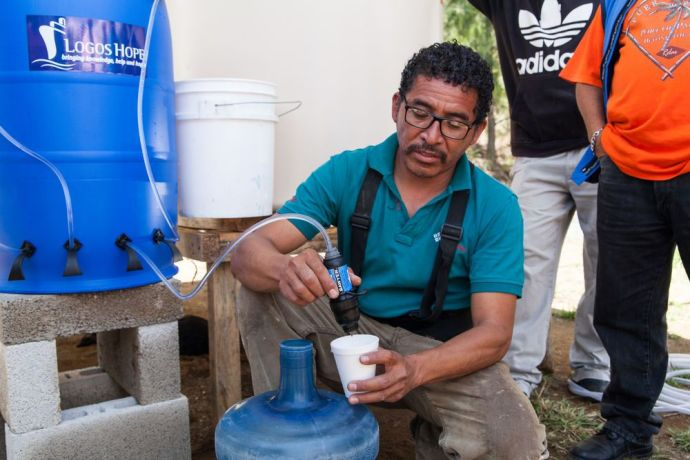 Guatemala: Puerto Quetzal, Guatemala :: An engineer demonstrates how to use a water filter donated from Logos Hope to a displaced community. More Info
