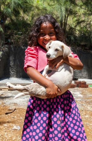 Guatemala: Puerto Quetzal, Guatemala :: Displaced from her home after a volcanic eruption, a young girl smiles with her puppy in their new rural community. More Info