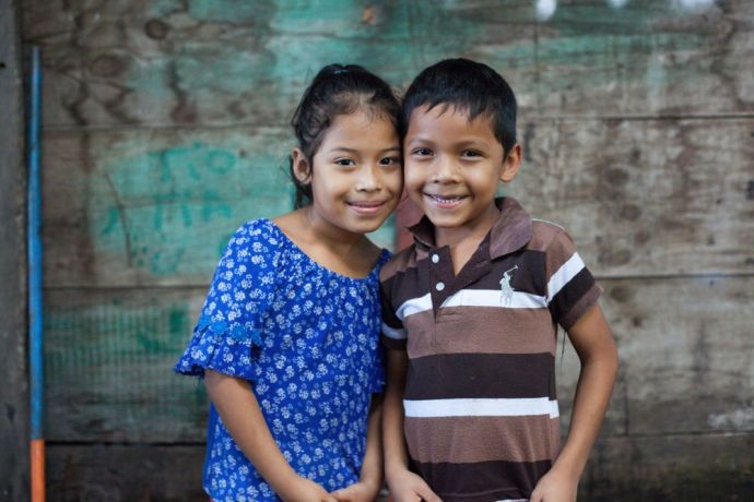 Guatemala: Puerto Quetzal, Guatemala :: A brother and sister smile in front of their home. More Info