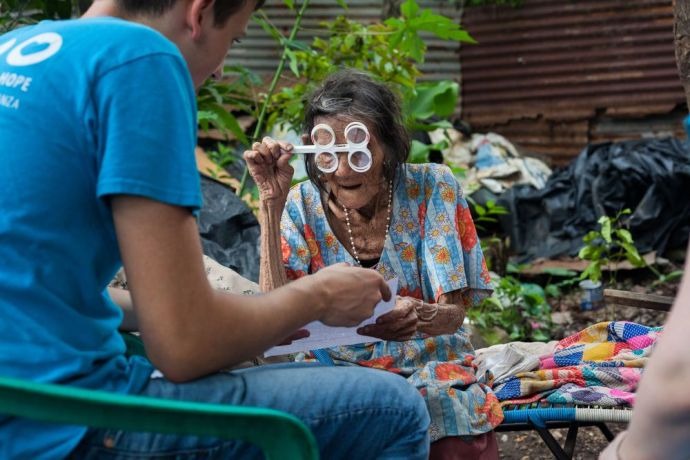 Guatemala: Puerto Quetzal, Guatemala :: Crewmembers from Logos Hope make a house visit so an elderly lady can still receive a free eye test, as she is too weak to walk to the village square, where the rest of the testing is taking place. More Info