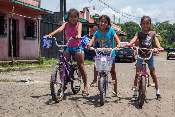 Guatemala: Puerto Quetzal, Guatemala :: Three young girls ride their bicycles outside. More Info