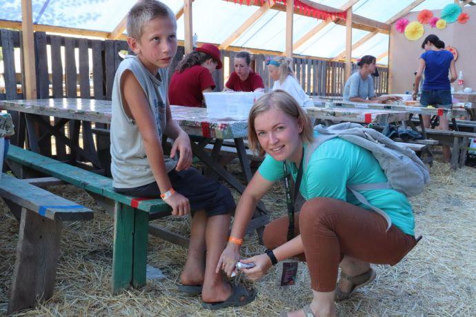 Ukraine: Yulia Niuniaieva tending to a wound at camp LELA for orphans, Odessa Ukraine More Info