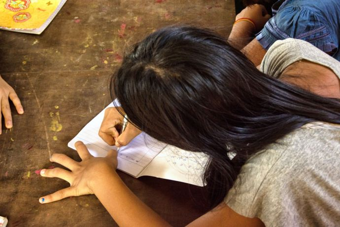 Thailand: A student takes notes during class at the School of Mercy, operated by OM MTI for 130 internally displaced Mon and Karen children in a village at the Thailand-Myanmar Border. More Info