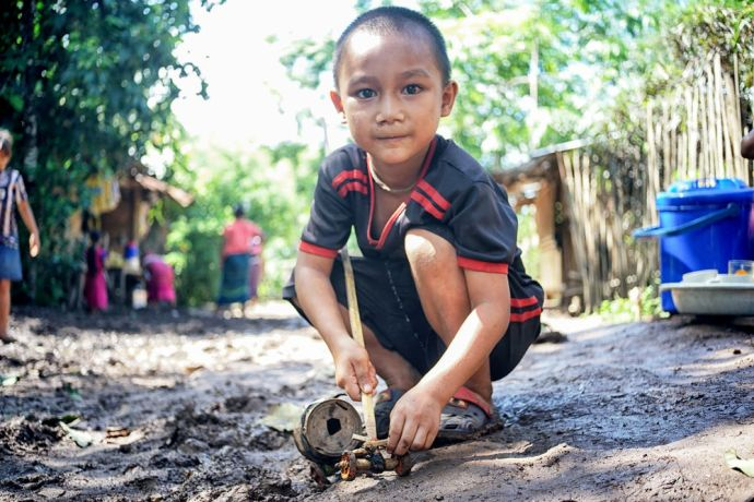 Myanmar: Portrait of a boy with a handmade toy in a village in Myanmar. More Info