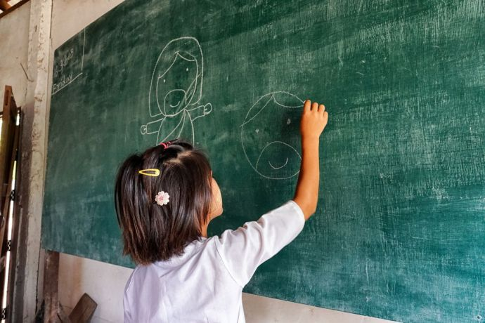 Thailand: A school girl draws on the chalkboard at the School of Mercy, operated by OM MTI for 130 internally displaced Mon and Karen children in a village at the Thailand-Myanmar Border. More Info