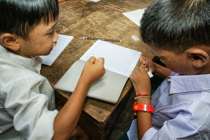 Thailand: Two school boys working together in class at the School of Mercy, operated by OM MTI for 130 internally displaced Mon and Karen children in a village at the Thailand-Myanmar Border. More Info