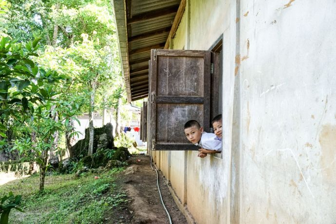 Myanmar: A couple boys looking out their classroom window at school in Myanmar More Info