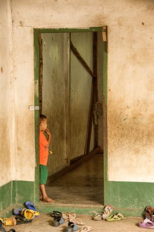 Thailand: A young boy stands hesitating in a classroom doorway on the first day of school at OM MTIs School of Mercy at the Thailand-Myanmar border. More Info