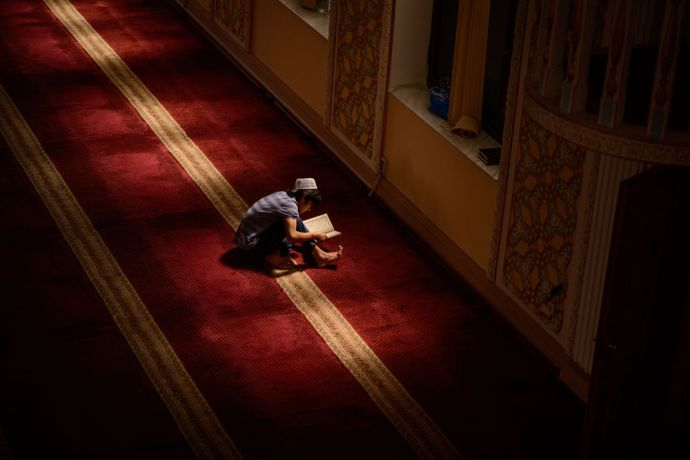 Central Asia: A young boy spends time reading after Friday prayer in a Central Asia mosque. More Info