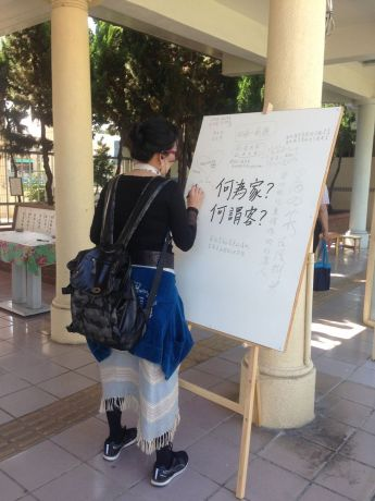 Taiwan: A local woman writes some associations about the words guest and home on a sheet of paper, that is part of an art exhibit put on by OM with Incarnate artist. More Info