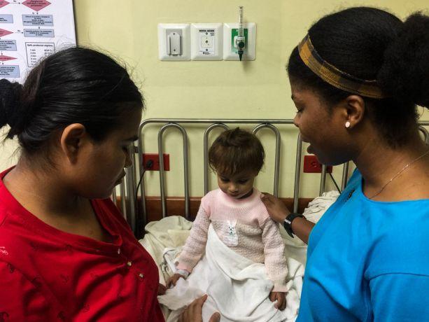 El Salvador: La Union, El Salvador :: Nikolae Beckford (Jamaica) prays for a mother and her daughter at a hospital. More Info