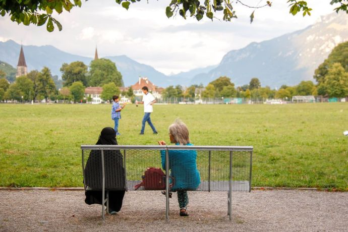 Switzerland: A volunteer talks to an Arab tourist during a summer outreach in Interlaken. Photo by Anja B. More Info