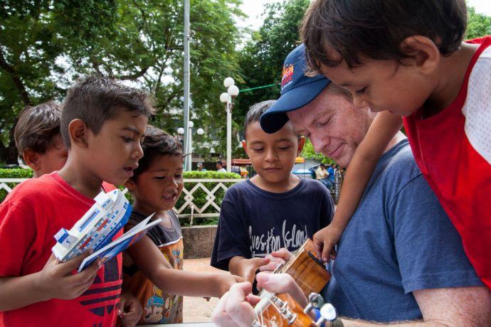 El Salvador: La Union, El Salvador :: Dan Bryer (UK) plays the ukulele with children at a park. More Info
