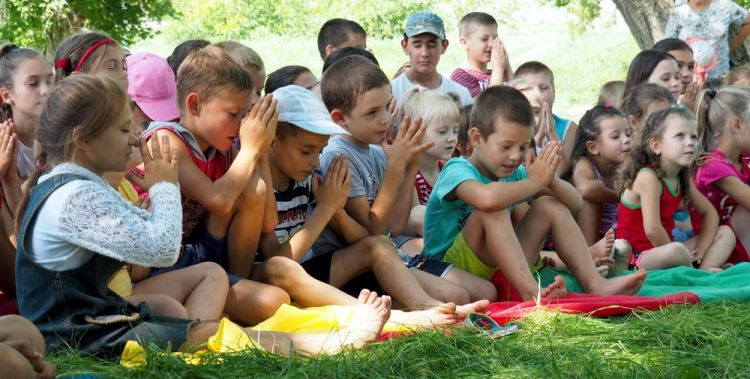 Moldova: Children praying at the end of a programme led by a 'River Adventure' outreach team in Zăluceni, a village with no evangelical church or known believers. The annual visits to this village have produced great openness, not only among the children but also their parents (many of whom attend the programmes) and the mayor. The 'River Adventure' is a short-term outreach by OM Moldova, which visits unreached areas along the river Nistru in northern Moldova every summer. More Info