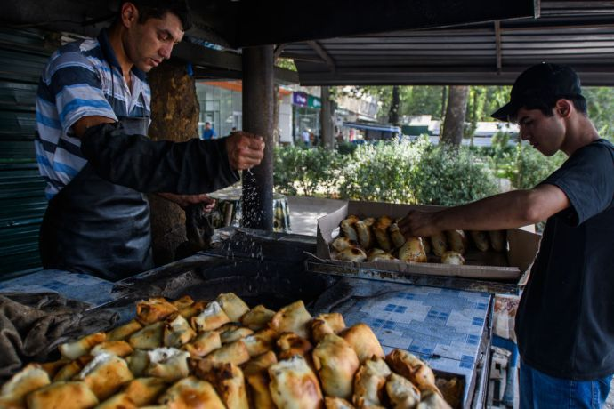 Central Asia: A man sprinkles water in the oven while baking bread in a traditional way in Central Asia.  Photo by Garrett N More Info