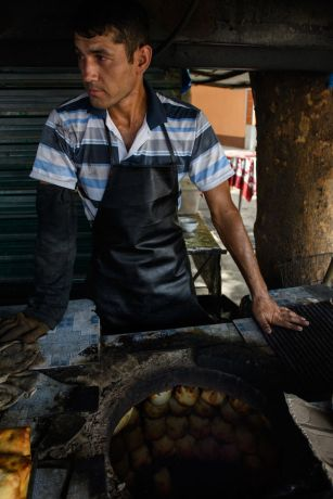 Central Asia: A man bakes bread in a traditional way in Central Asia.  Photo by Garrett N More Info