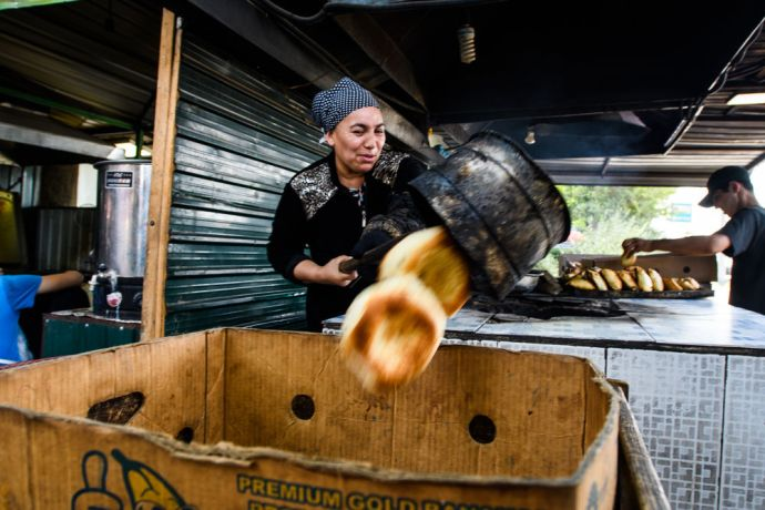 Central Asia: A woman bakes bread in a traditional way in Central Asia.  Photo by Garrett N More Info