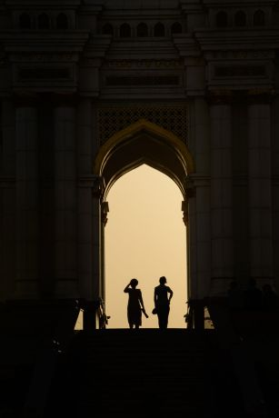 Central Asia: Two women are silhouetted by the evening light as they stand under the arch of a local monument in Central Asia.  Photo by Garrett N More Info