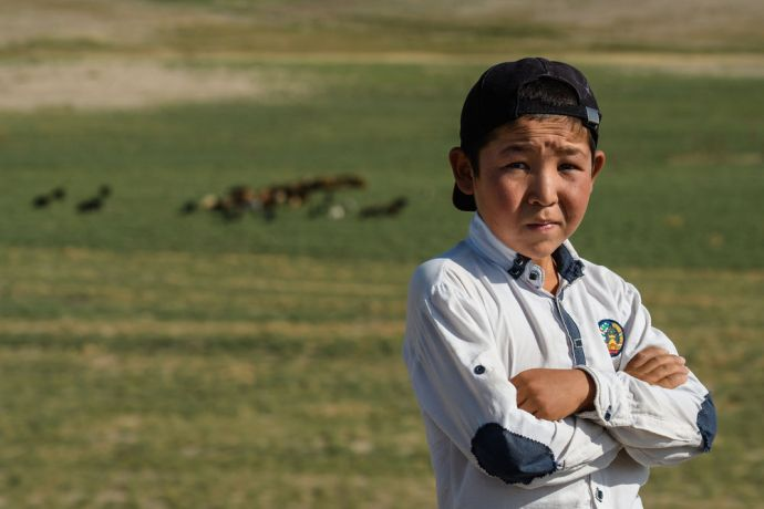 Central Asia: A young boy herds his families sheep and goats across un-occupied land, ensuring their safety and proper care in Central Asia.  Photo by Garrett N More Info