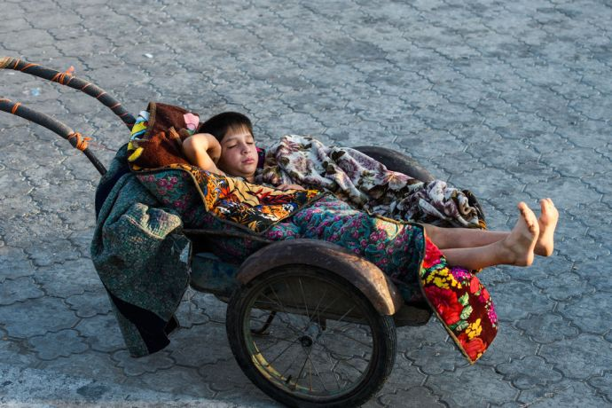 Central Asia: A young boy sleeps on a wheelbarrow while his mom sells produce at a market in Central Asia.  Photo by Garrett N More Info