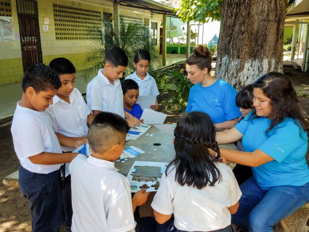 Costa Rica: Puntarenas, Costa Rica :: Roselyn Faensen- Glienke (Germany) and Valeria Balderas (Mexico) help a group of schoolchildren assemble cardboard models of Logos Hope. More Info