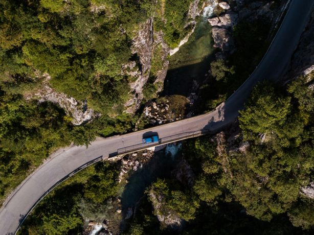 Kosovo: Drone image of a blue car driving over a bridge near Peja kosovo.  Photo by Garrett N More Info