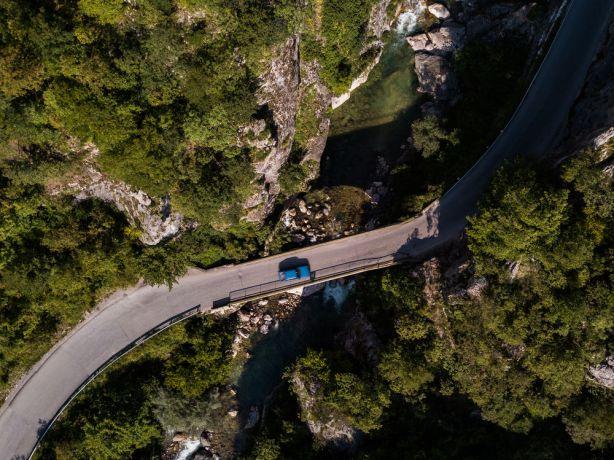 Kosovo: Drone image of a blue car driving over a bridge near Peja kosovo.  Photo by Garrett N More Info